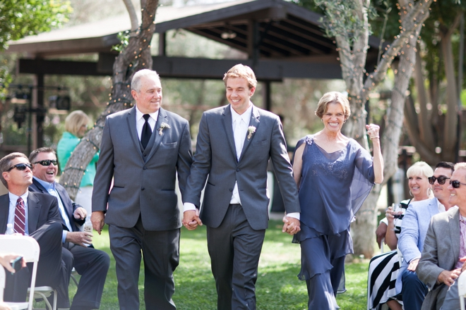 The grooms parents walking him down the aisle, look how happy his mother is!
