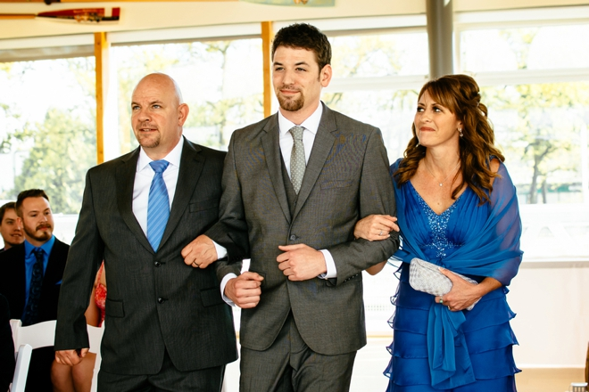 The groom and his parents walking down the aisle