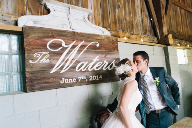 Kissing in front of hand painted wedding sign