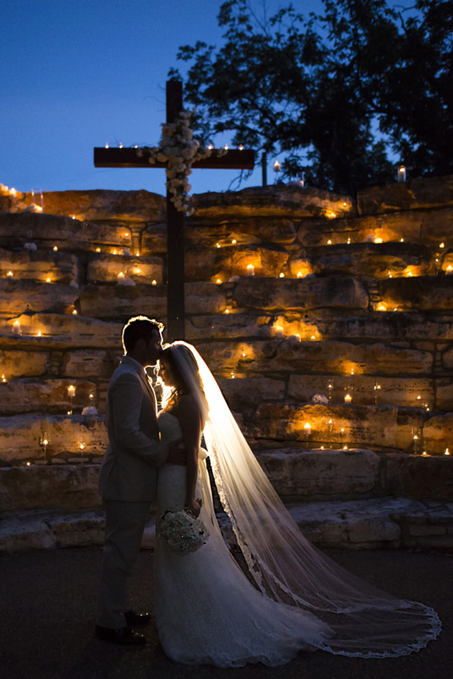 Bride and Groom embrace under candlelit cross