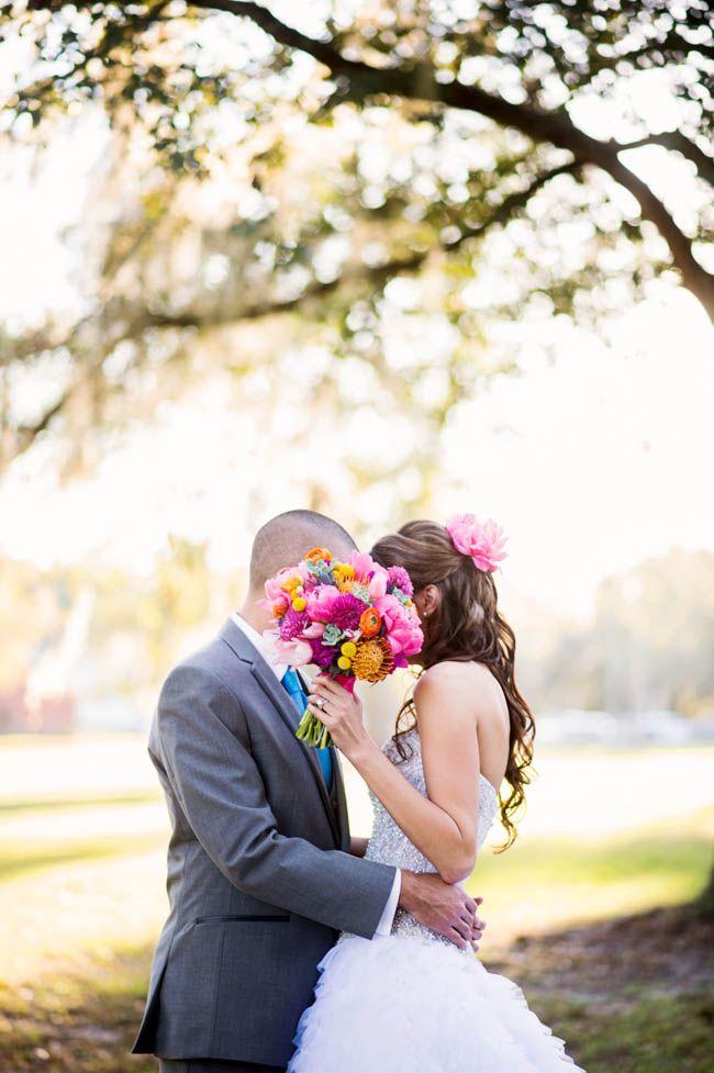 Bride and Groom kissing behind flowers
