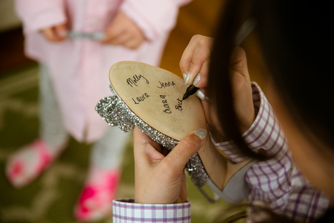 Bridesmaids signing the bottom of the brides shoes