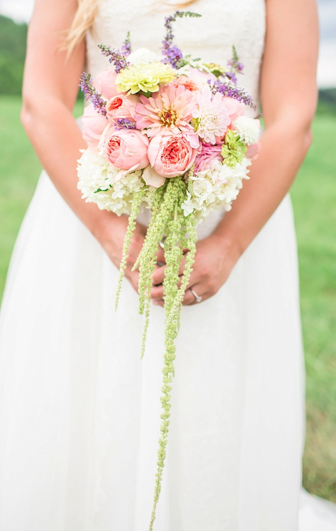 Bride holding gorgeous bouquet full of cabbage roses, hydrangea and amaranthus