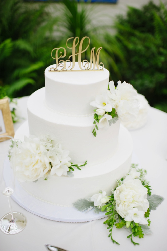 Beautiful, simple white wedding cake embellished with green and white flowers.