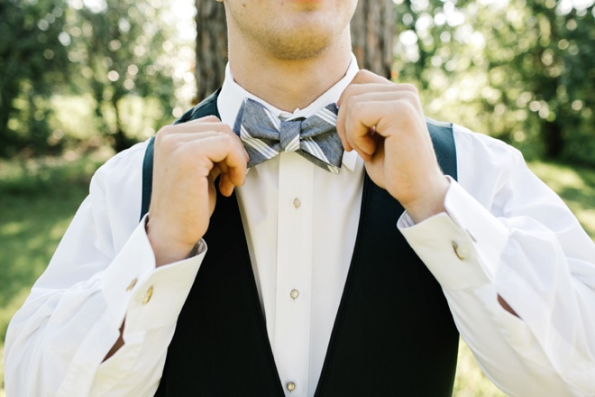 Groom fixing his bow tie.