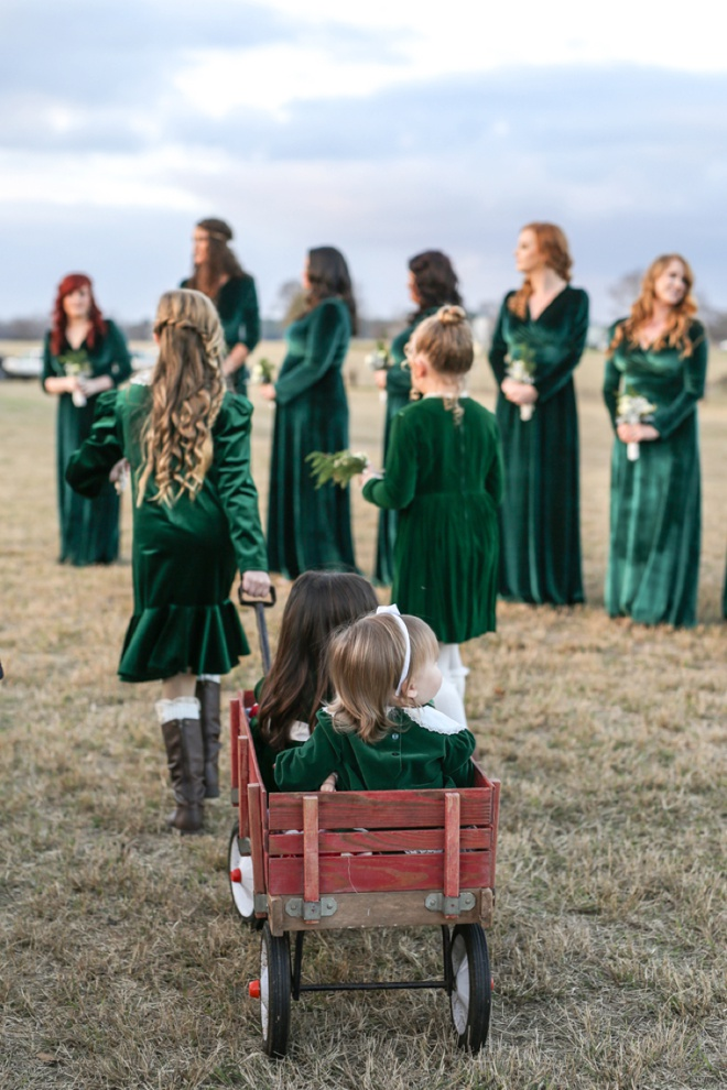Little flower girls getting pulled down the aisle in a wagon!