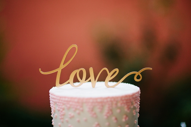 We're swooning over this gorgeous gold calligraphy love cake topper on this two tiered wedding cake!