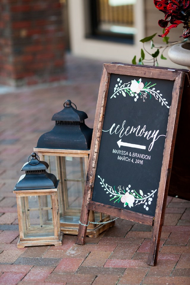 Super cute hand lettered chalkboard wedding sign and lanterns leading the way into their ceremony!
