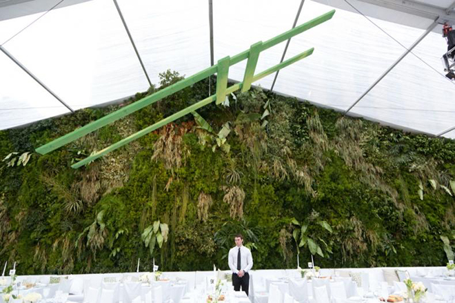 a wall of greenery in your wedding tent could not be more dreamy