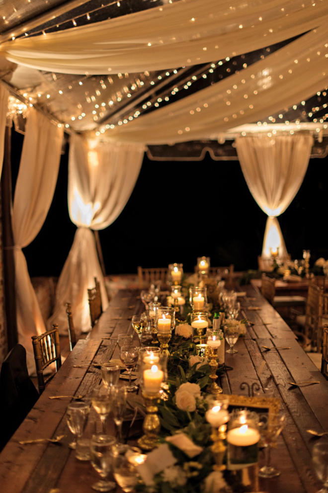 a combination of fabric and twinkle lights make for a beautiful layered look in a wedding tent