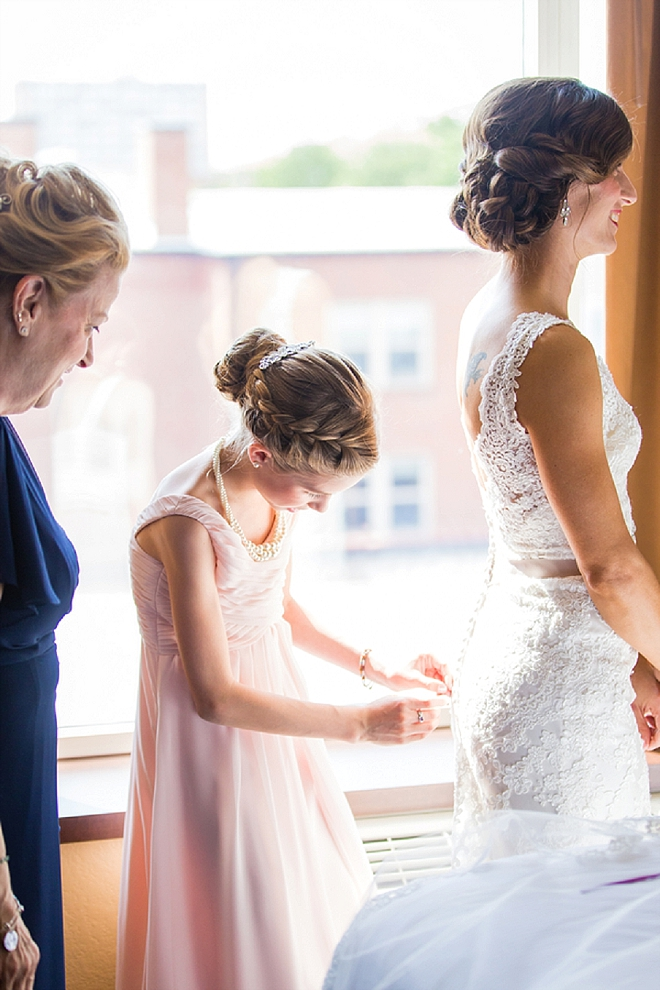 We love this snap of the Bride's mother and daughter helping her into her dress!