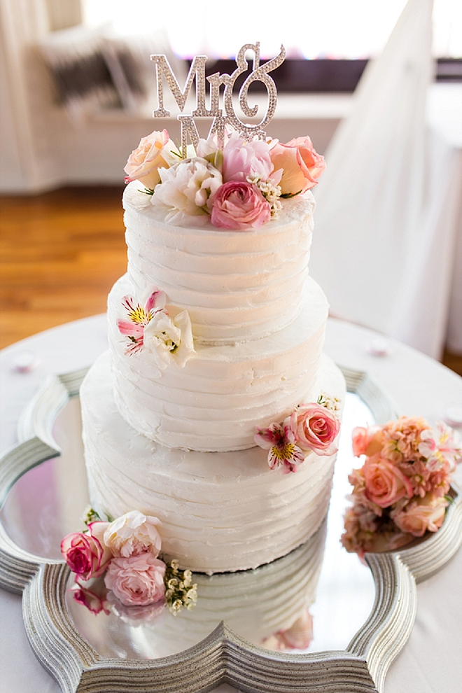 We're in love with this classic and blush wedding cake and Mr. and Mrs. cake topper!