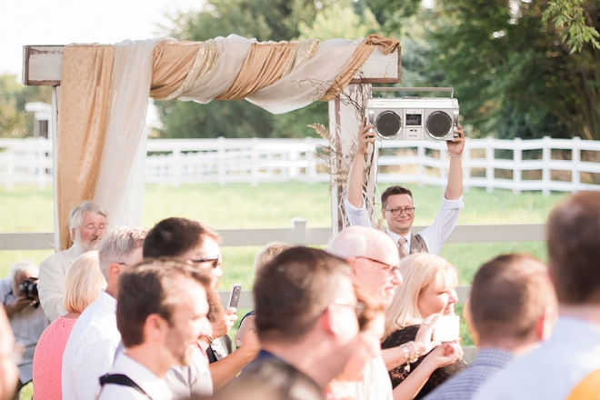 Such a fun shot of the Groom holding a boom box while his bride walks down the aisle!