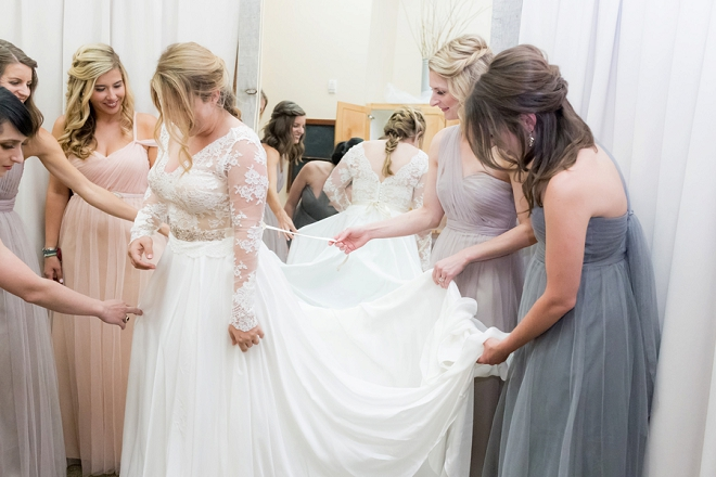 Great shot of the Bride getting her finishing touches from her Bridesmaids!