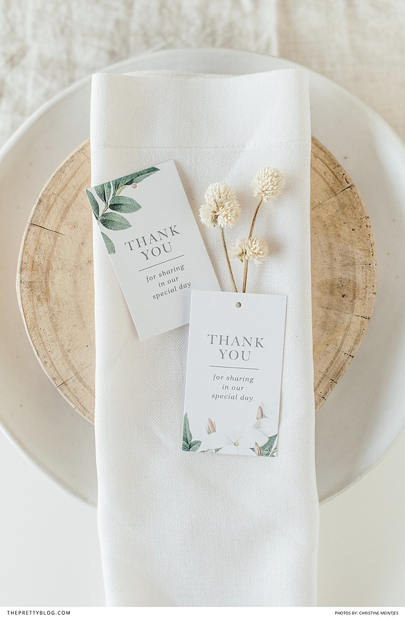 Wood and white table settings with a wedding thank you card.