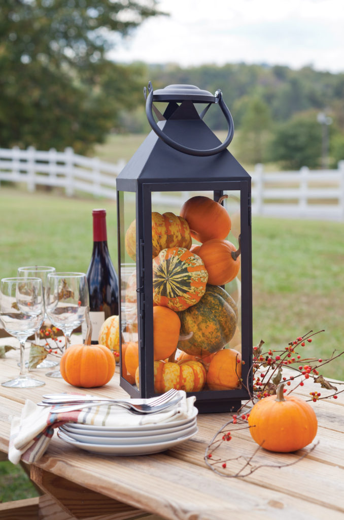 Beautiful black lanterns with mini pumpkins inside.  Easy and affordable DIY centrepiece for a wedding or party.