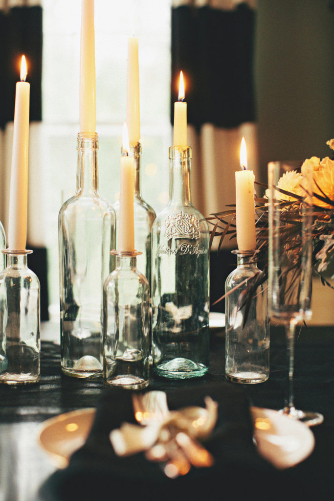 DIY wine bottle candle holders make a great wedding centrepiece for a fall or halloween wedding.