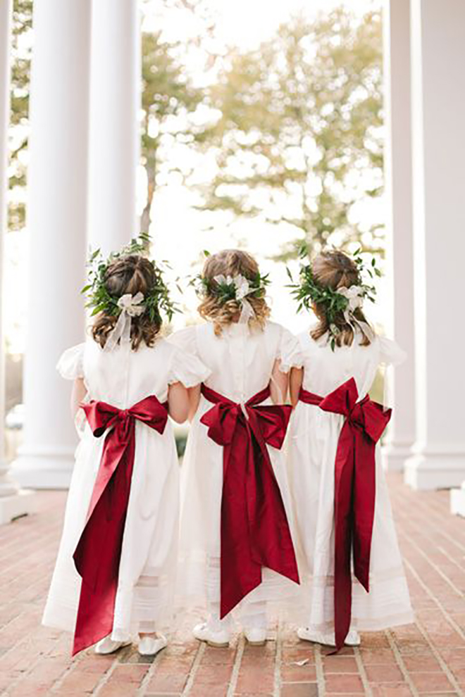 Flower girls in greenery crowns and red bows is the perfect touch of Christmas.