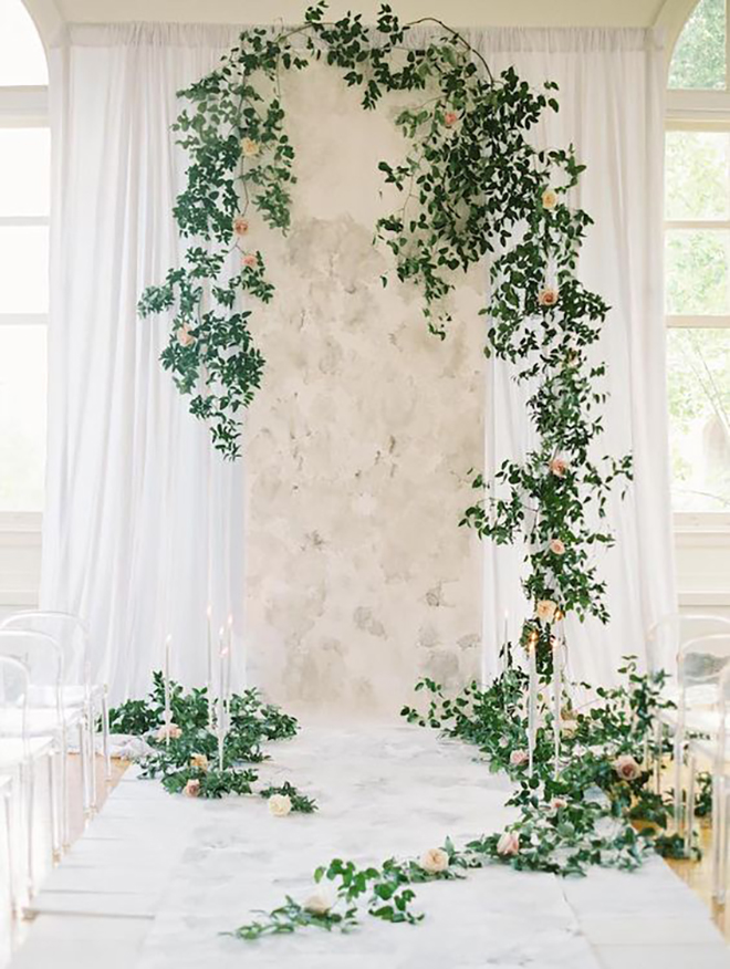 I lush green and marble ceremony backdrop is beautifully romantic.