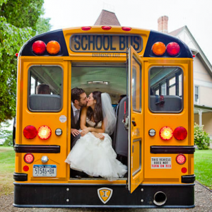 Adorable bride and groom kissing in the back of a school bus!