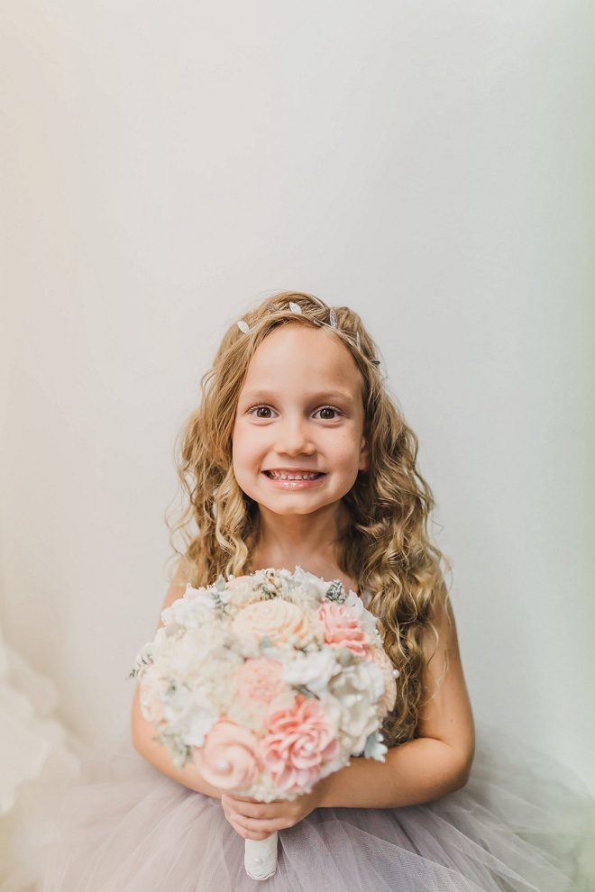How adorable is this flower girl?! She won our hearts with her adorable bouquet and smile! See more adorable snaps from this sweet backyard wedding!