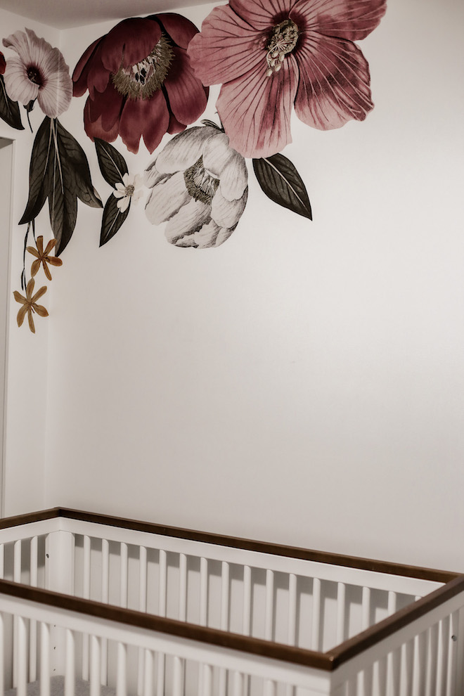This boho, romantic baby girl nursery is stunning! Love the walnut, minimalist crib and the floral wall decals.