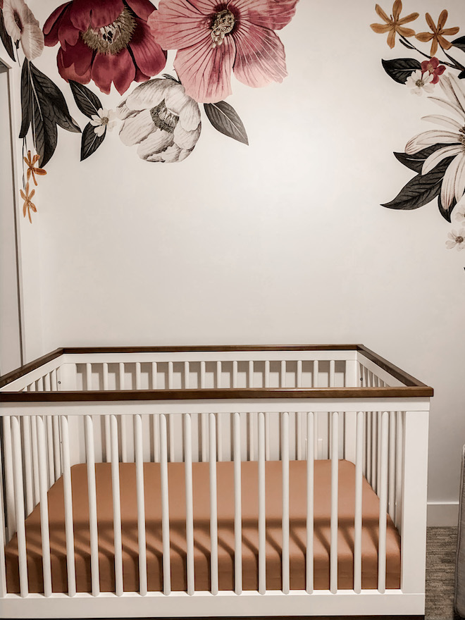 Obsessed with this burnt orange/rust crib sheet and the muted floral wall decals. Such a pretty idea for a baby girl's nursery!